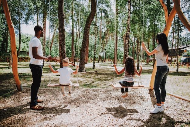 Belo dia de sol na família de parque no parque infantil