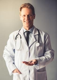 Belo doutor maduro no jaleco branco está segurando comprimidos.