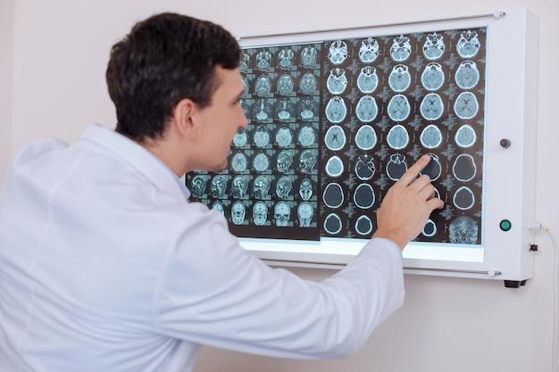 Belo e agradável jovem médico apontando para o cérebro humano retratado na foto de raio-x e olhando para ele enquanto encontra o problema