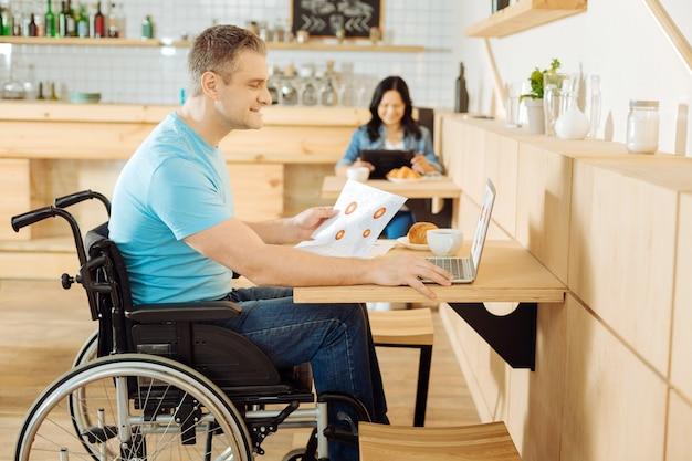 Belo e inspirado homem deficiente sentado em uma cadeira de rodas, segurando uma folha de papel e trabalhando em seu laptop