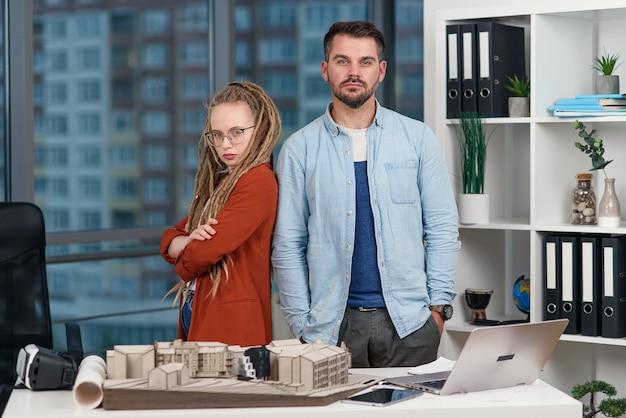 Belo e jovem engenheiro profissional fica de costas um para o outro com uma bela colega com
