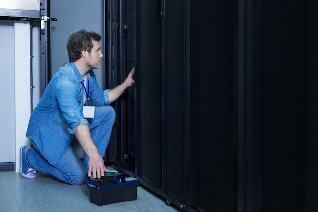 Belo e simpático engenheiro do sexo masculino sentado sobre um joelho e pegando o servidor de rack enquanto o instala no servidor de rede