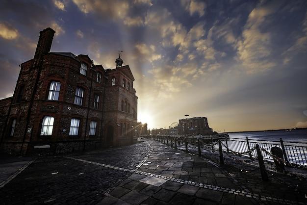 Belo edifício perto do mar em liverpool durante o pôr do sol