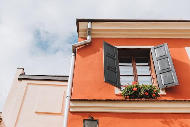 Belo edifício vermelho com flores fora das janelas e persianas velhas Foto Premium