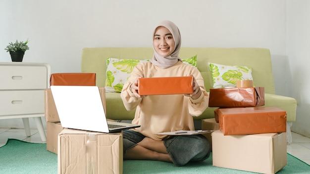 Belo empresário asiático mostrando produtos prontos para enviar