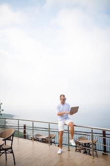Belo empresário jovem e bem sucedido trabalhando com laptop olha para o mar mediterrâneo. ele está vestindo uma camisa e shorts brancos. trabalho remoto de férias. conceito de férias