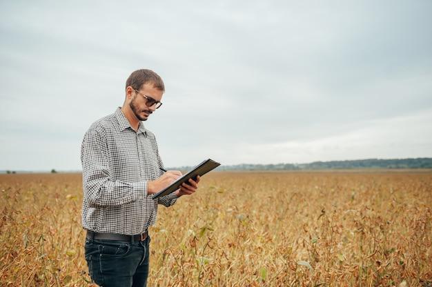 Belo engenheiro agrônomo segura um tablet touch pad no campo de soja e examina as colheitas antes da colheita
