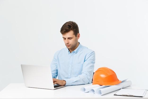 Belo engenheiro está usando um notebook para o trabalho. ele está sentado à mesa e sorrindo. copie o espaço na lateral.