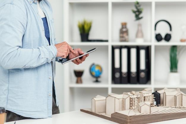 Belo engenheiro trabalha no projeto de construção, examina uma maquete do futuro edifício e faz algumas anotações no tablet pc