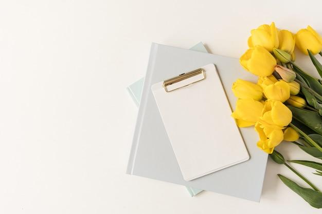 Belo espaço de trabalho de escritório moderno com prancheta e artigos de papelaria e flores tulipa. flatlay, mesa de trabalho minimalista com vista superior. folha de papel em branco com espaço de cópia de maquete