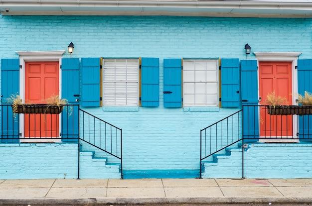 Belo esquema de cores das escadas que levam a apartamentos com portas e janelas semelhantes