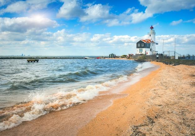 Belo farol na costa do mar e o céu azul com nuvens ao pôr do sol na primavera na holanda. paisagem com areia amarela, mar e farol. paisagem marinha. vista do mar à noite na europa