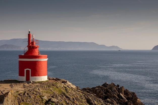 Belo farol vermelho com o mar ao fundo. localizado em cabo do home. cangas, galicia, espanha