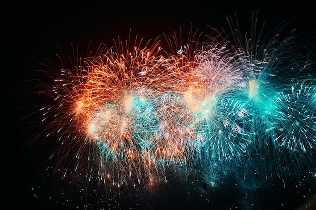Belo fogo de artifício à noite. explosão colorida no céu negro. traço de luz com explosão brilhante e faíscas de fogos de artifício explodindo no céu escuro da noite. exposição longa