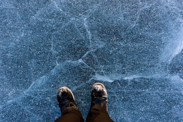 Belo gelo do lago baikal com rachaduras abstratas com sapatos. vista do topo