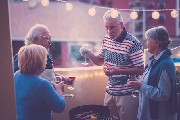 Belo grupo de pessoas adultas caucasianos em felicidade, ficarem juntos para jantar ao ar livre no terraço. conceito de amor e amizade com uma vista incrível. férias e lazer.