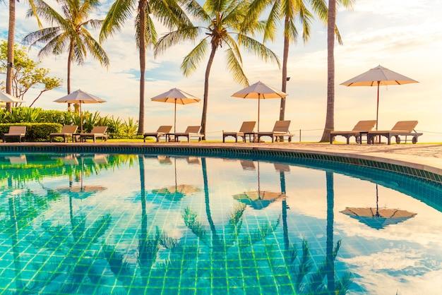 Belo guarda-chuva de luxo e cadeira ao redor da piscina ao ar livre no hotel e resort com coqueiro no céu do pôr do sol ou nascer do sol conceito de férias e férias