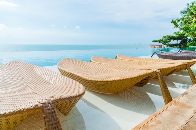 Belo guarda-chuva de luxo e cadeira em torno da piscina ao ar livre no hotel e resort