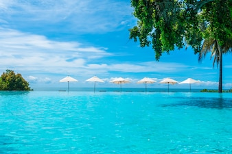Belo guarda-chuva de luxo e cadeira em torno da piscina no hotel e resort
