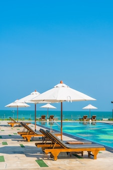 Belo guarda-chuva e cadeira em volta da piscina no hotel e resort