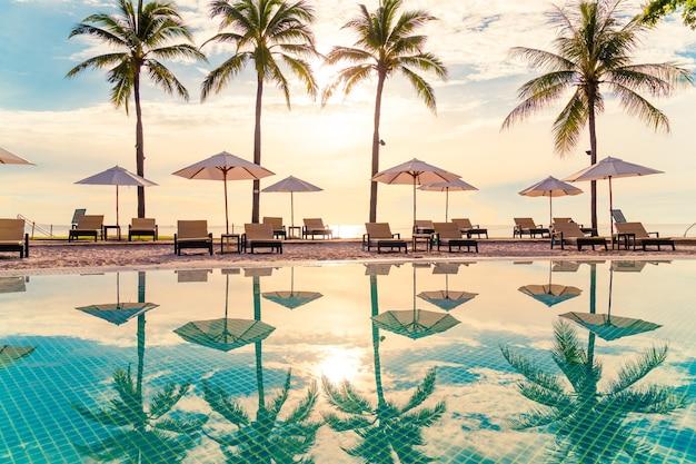 Belo guarda-sol de luxo e cadeira ao redor da piscina ao ar livre no hotel e resort com coqueiro no céu do pôr do sol ou nascer do sol - conceito de férias e férias