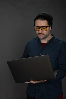 Belo hipster com barba por fazer com boné de malha trabalhando com o laptop em um fundo cinza