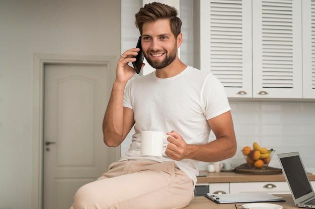 Belo homem adulto falando ao telefone