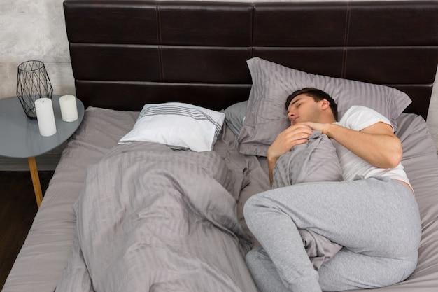 Belo homem cansado de pijama dormindo sozinho sem cobertor e abraçando um travesseiro em uma cama estilosa em tons de cinza e perto da mesa de cabeceira com velas em um quarto em estilo loft