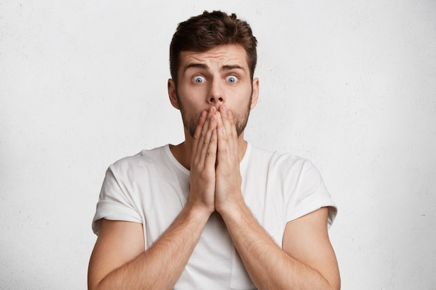 Belo homem chocado e aterrorizado com olhos esbugalhados cobre a boca com as mãos e vê algo horrível