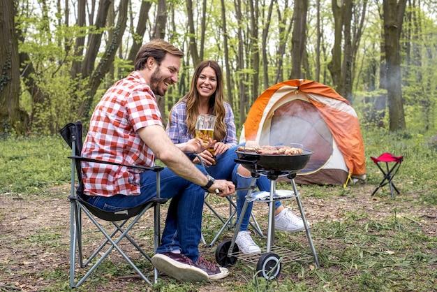 Belo homem feliz preparando churrasco ao ar livre enquanto bebe cerveja
