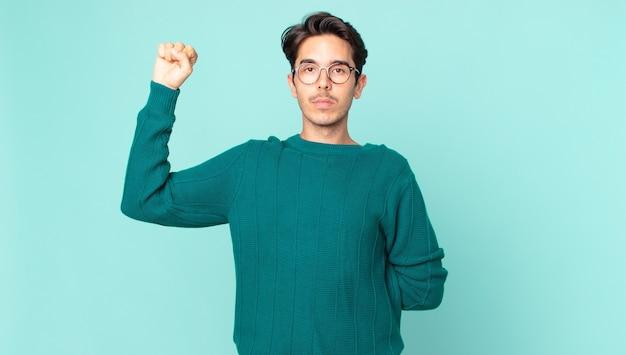 Belo homem hispânico se sentindo sério, forte e rebelde, levantando o punho, protestando ou lutando pela revolução