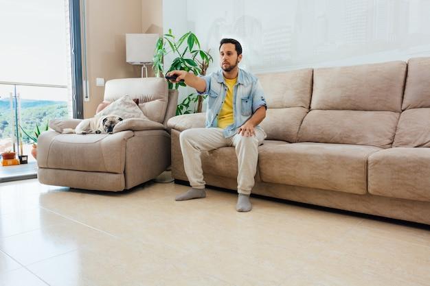 Belo homem hispânico sentado em um sofá assistindo tv