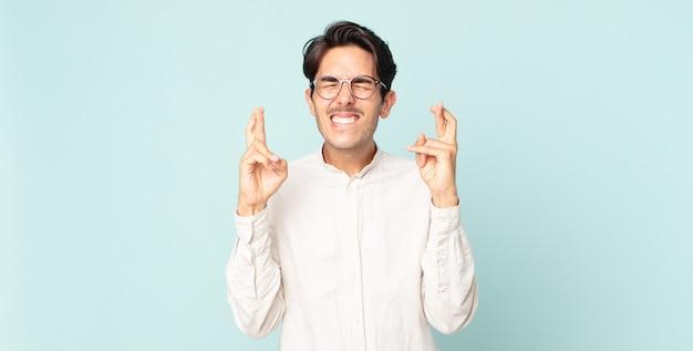 Belo homem hispânico sorrindo e cruzando os dois dedos ansiosamente, sentindo-se preocupado e desejando ou esperando por boa sorte