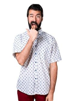 Belo homem moreno com barba fazendo gestos de vomitar