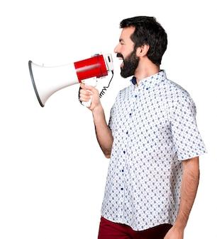 Belo homem moreno com barba gritando por megafone