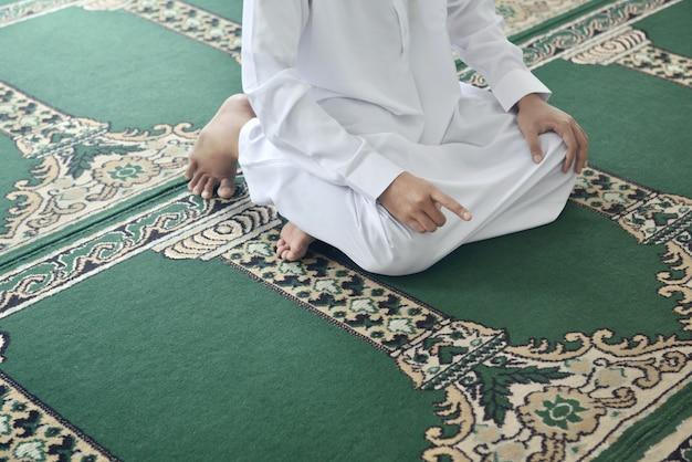 Belo homem muçulmano asiático, levantando a mão e rezando