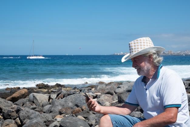 Belo homem sênior sentado nas rochas da praia com um chapéu de cowboy. olhando para o telefone e sorrindo. céu azul e mar atrás dele. férias ou conceito de aposentadoria.
