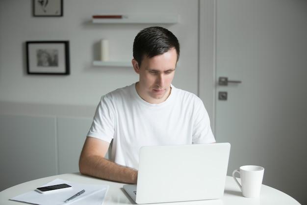 Belo homem sentado na mesa trabalhando com laptop