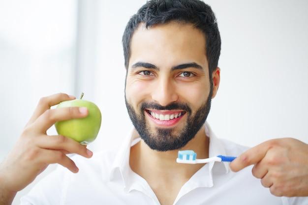 Belo homem sorridente, escovando os dentes brancos saudáveis com escova.
