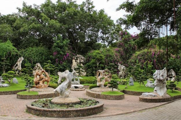 Belo jardim botânico com figuras decorativas de pedra, arbustos aparados nas árvores, grama verde e flores roxas.