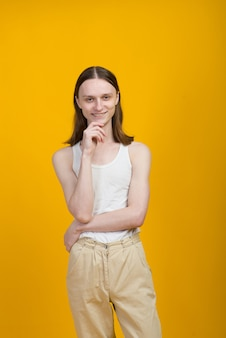 Belo jovem andrógino. testes de modelo em parede amarela