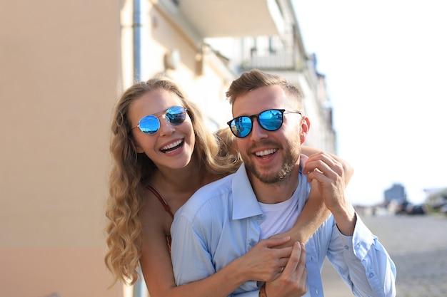 Belo jovem casal apaixonado, caminhando ao ar livre na rua da cidade, se abraçando.