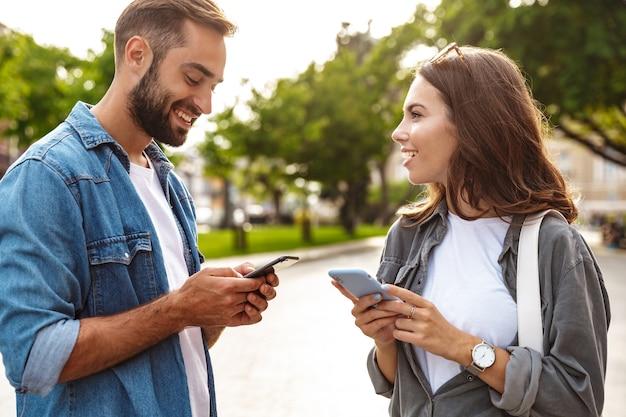 Belo jovem casal apaixonado caminhando ao ar livre nas ruas da cidade, usando telefones celulares