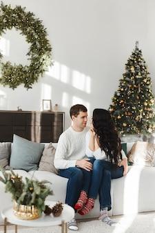 Belo jovem casal apaixonado em meias com padrão de natal, olhando um para o outro na sala decorada para o natal.