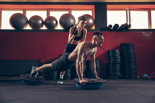 Belo jovem casal desportivo treino no ginásio juntos. homem caucasiano treinando com treinadora. conceito de esporte, atividade, estilo de vida saudável, força e poder. malhar com pesos. puxar para cima.