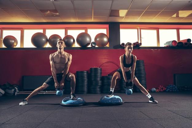 Belo jovem casal desportivo treino no ginásio juntos. homem caucasiano treinando com treinadora. conceito de esporte, atividade, estilo de vida saudável, força e poder. malhar com pesos.