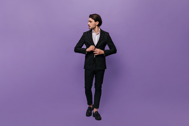 Belo jovem cavalheiro em um terno elegante, camisa branca e sapatos pretos, endireitando o paletó e olhando para o lado