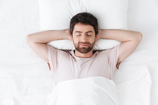 Belo jovem de manhã descansa na cama