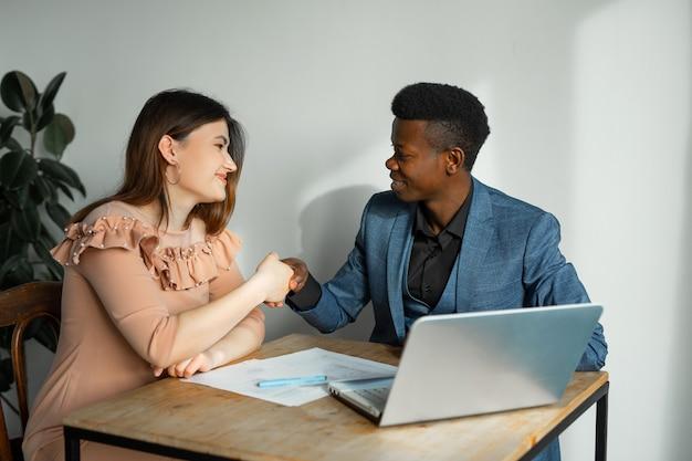 Belo jovem e mulher trabalhando no escritório com laptop