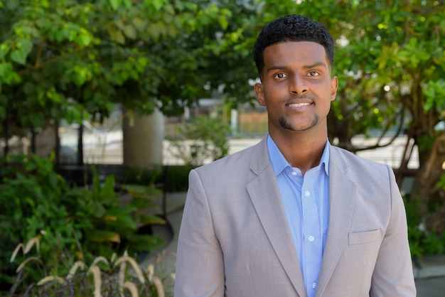 Belo jovem empresário africano ao ar livre no parque sorrindo